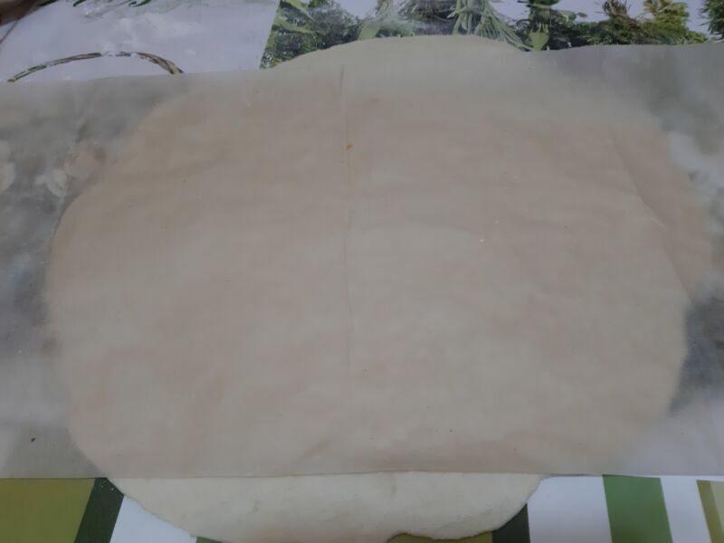 Раскатываем тесто с помощью скалки и пергаментной бумаги.